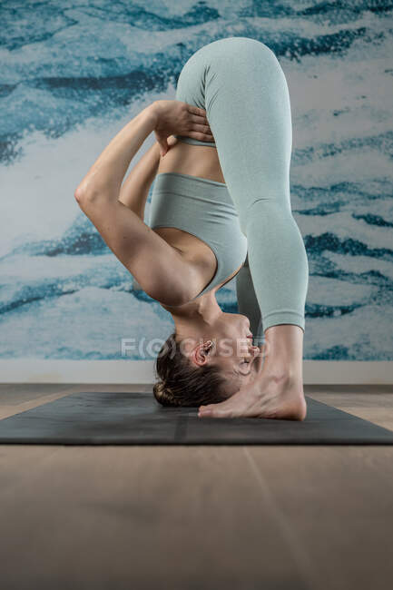 Side view full body of slim barefoot female with closed eyes bending forward while meditating in Big Toe position — Stock Photo