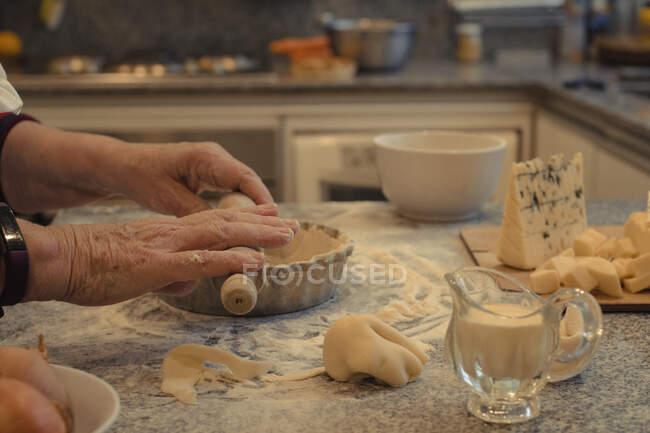 Анонимный шеф-повар с кондитерской коркой над столом с выпечкой и разнообразными сырами во время приготовления — стоковое фото