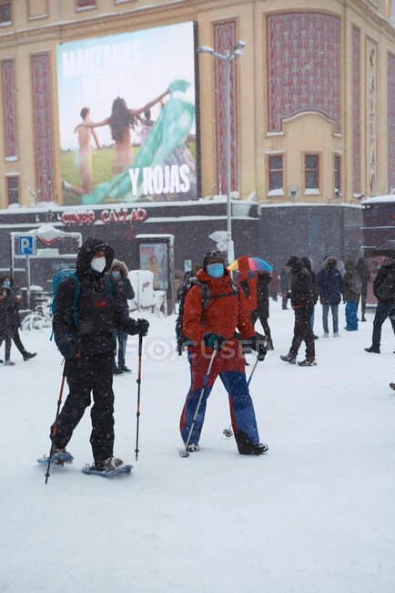 9 січня 2021 року - Мадрид (Іспанія): у день зимового відпочинку чоловіки без облич вдягають теплий одяг на лижних ковзанах з полюсами на сніговій міській площі. — стокове фото