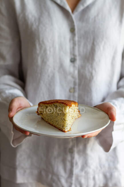 Crop anonymous female standing with piece of homemade sponge cake on plate prepared for breakfast — Stock Photo