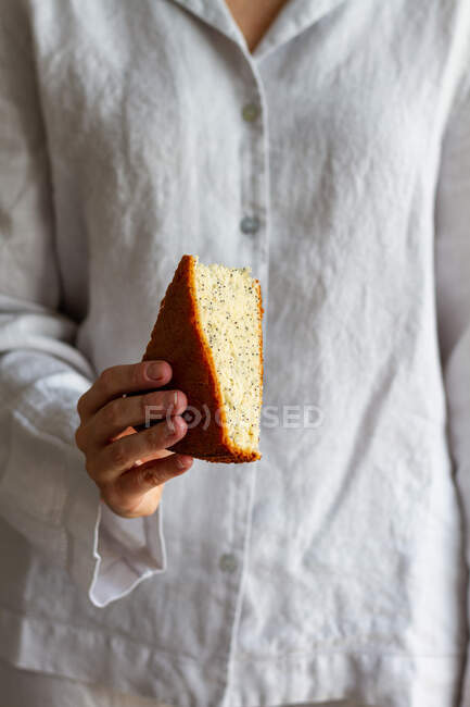 Невідома жінка стоїть зі шматочком домашнього торта для губки, приготованого на сніданок. — стокове фото