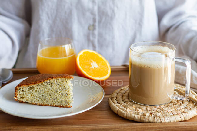 Unrecognizable crop woman with wooden tray served with cup of coffee and sponge cake for breakfast at home — Stock Photo