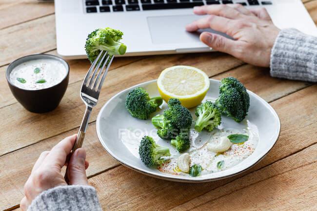 Анонімна жінка з смачною приготованою брокколі на виделці, яка переглядає інтернет за столом — стокове фото
