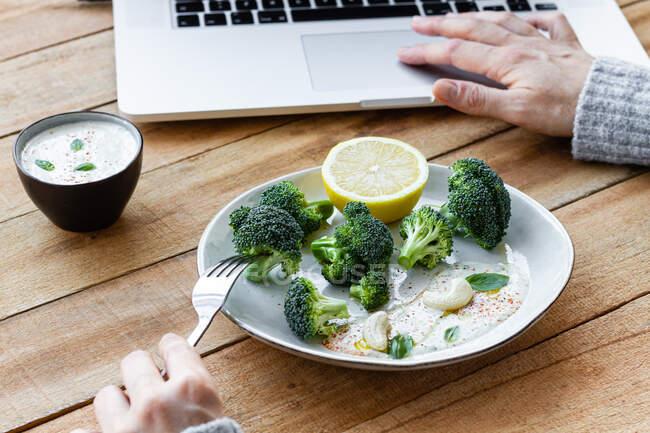 Cultivo femenino anónimo con delicioso brócoli cocido en tenedor navegar por Internet en netbook en la mesa - foto de stock