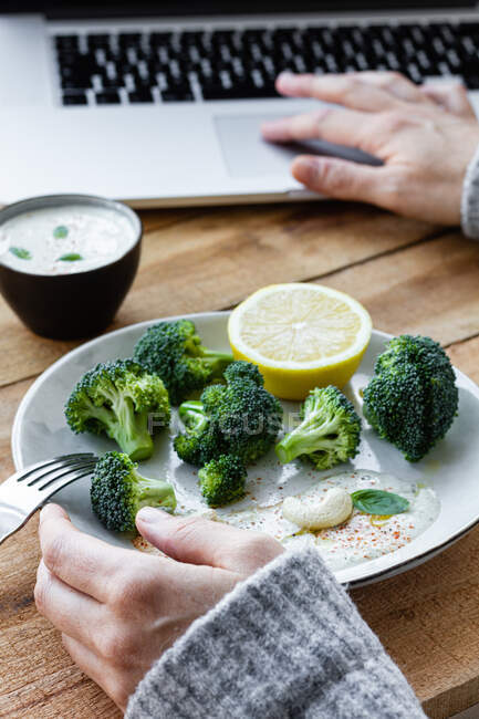 Crop anonymous female with delicious cooked broccoli on fork browsing internet on netbook at table — Stock Photo