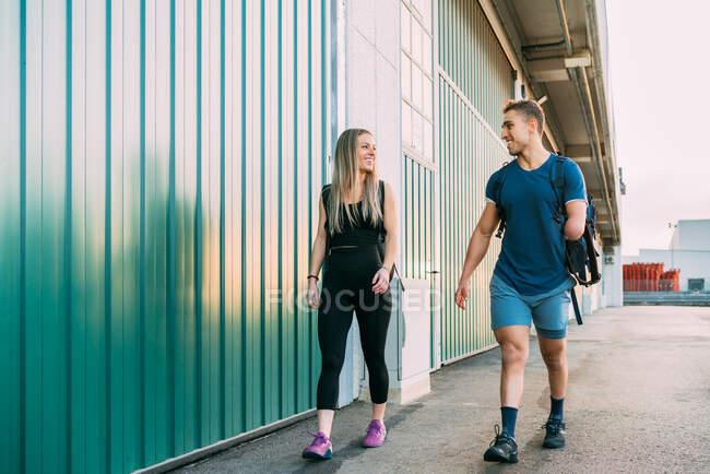 Молодые сидят счастливые спортсменки и спортсменки-инвалиды, идя вместе в спортзал и глядя друг на друга. — стоковое фото
