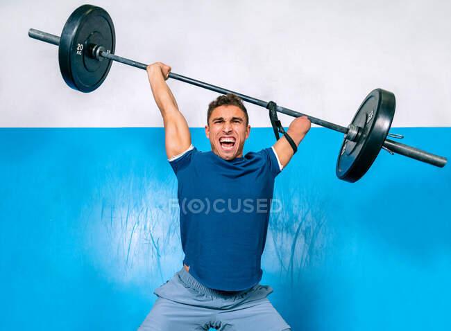 Сильний чоловічий спортсмен без ручного вереску під час тренувань під час тренування спортивного устаткування в гімназії. — стокове фото
