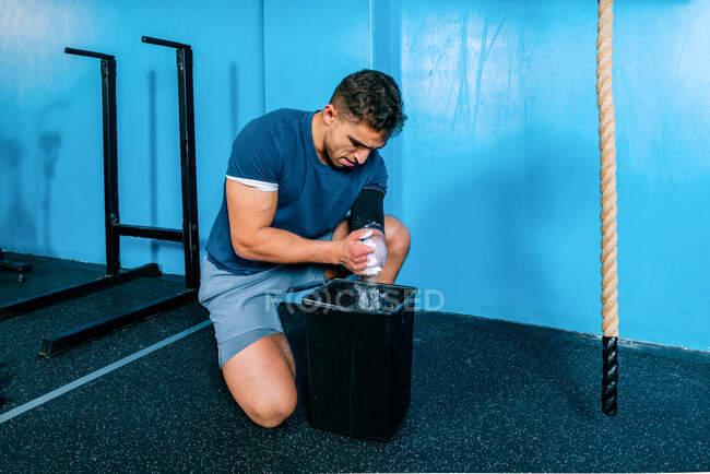 Пригодный спортсмен, нанося тальковый порошок на руки перед тренировкой в спортзале. — стоковое фото