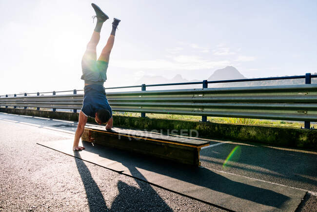 Back view of unrecognizable handicapped male athlete in sports clothes standing on hands on fenced bridge with bench in sunlight — Stock Photo