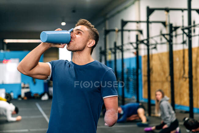 Молодой спортсмен-инвалид в спортивной форме пьет напиток из бутылки и смотрит вверх во время тренировки рядом с неузнаваемыми партнерами в гимназии — стоковое фото