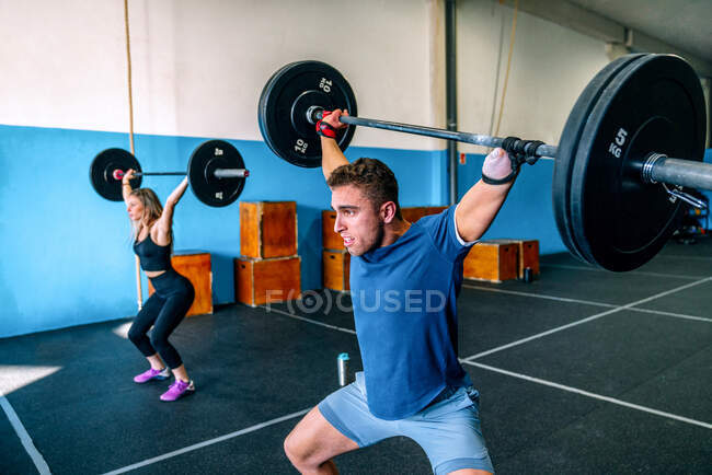 Powerful sportswoman with handicapped male athlete lifting heavy weights and looking forward during functional training in gymnasium — Stock Photo