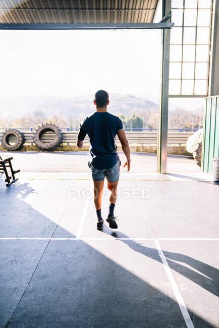 Vista posterior de un atleta masculino anónimo discapacitado en ropa deportiva paseando por el suelo con sombras en el gimnasio en un día soleado - foto de stock