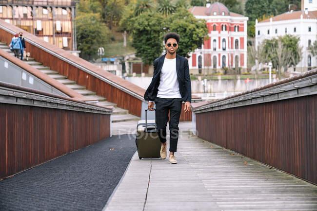 Афроамериканський турист з валізою йде по похилій вулиці в місті і дивиться на камеру. — стокове фото