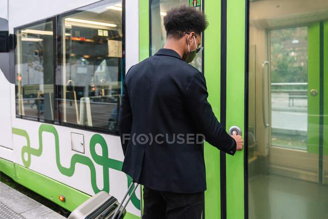 Повернення до афроамериканського туриста з маскою і з валізою натискання кнопки і в'їзд у сучасний поїзд стоячи на платформі під час коронавірусу — стокове фото