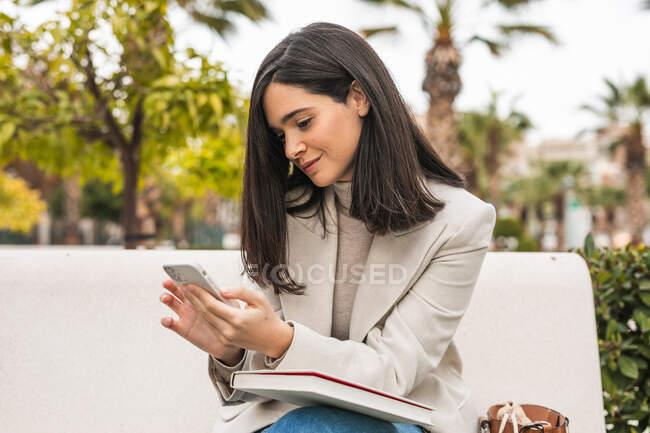 Imprenditrice concentrata che utilizza smartphone in strada mentre controlla i messaggi in e-mail — Foto stock