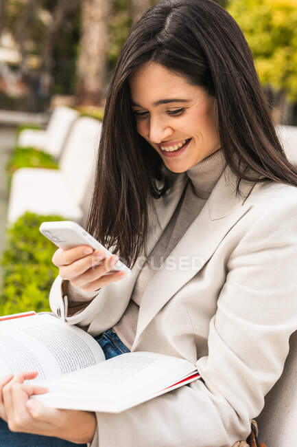 Smile female entrepreneur using smartphone in street while checking messages in email — Stock Photo