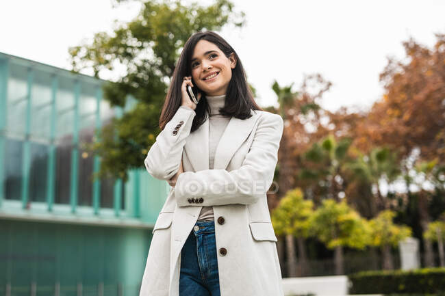 Low angle of glad female entrepreneur talking on smartphone and standing in street while discussing business project and looking away — Stock Photo