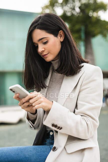 Vista laterale di imprenditrice concentrata che utilizza lo smartphone in strada mentre controlla i messaggi in e-mail — Foto stock