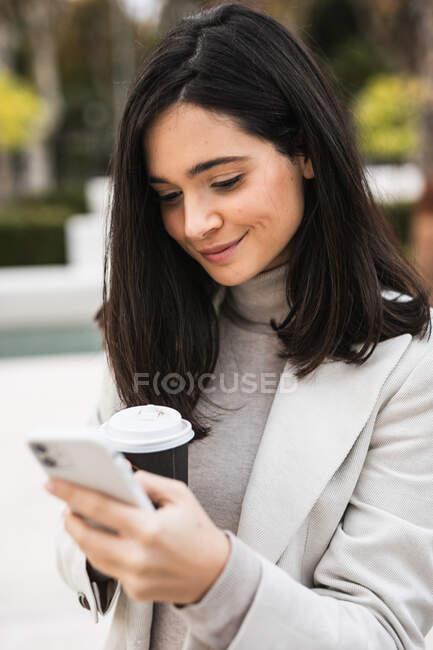 Lächelnde Unternehmerin benutzt Smartphone auf der Straße beim Kaffeetrinken — Stockfoto