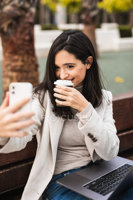 Delighted young female entrepreneur sitting on bench with laptop and taking self portrait with coffee to go in paper cup while using smartphone — Stock Photo