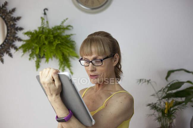 Erwachsene Frauen in Freizeitkleidung sehen Video auf modernem Tablet im hellen Wohnzimmer — Stockfoto