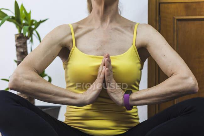 Анонимная женщина в активной медитации, сидя в позе лотоса с руками в намасте жест в светлой гостиной — стоковое фото