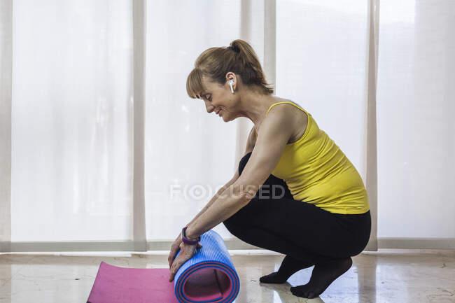 Взгляд сбоку улыбающаяся взрослая женщина в платье, слушающая любимую музыку и катящая коврик для йоги после интенсивных тренировок в легком фитнес-центре — стоковое фото