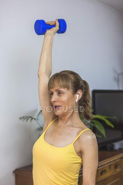 Усмішка, що вписується в жовту верхню частину, робить тренування на руках з ніздрями під час роботи в сучасному фітнес-центрі. — стокове фото