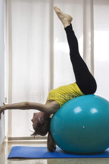 Вид сбоку подходит женщине в спортивной одежде, растягивающей мышцы спины на большом мяче для йоги в легком фитнес-центре — стоковое фото