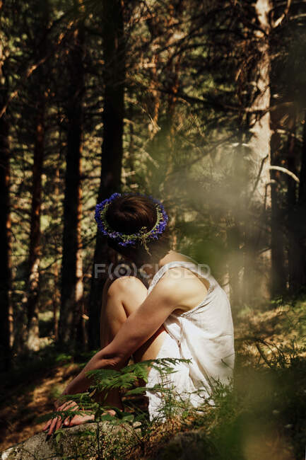 Side view of unrecognizable romantic thoughtful lady with short hair in summer dress and floral wreath embracing knees while sitting on grass in lush forest — Stock Photo