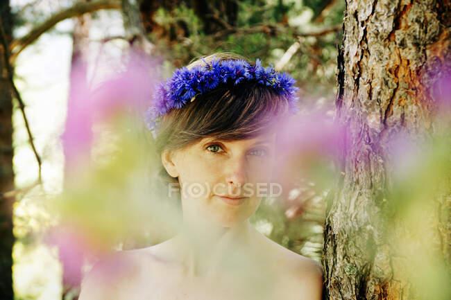 Femme adulte paisible avec épaule nue et couronne florale sur la tête debout près d'un arbre et regardant la caméra par une journée ensoleillée en forêt — Photo de stock