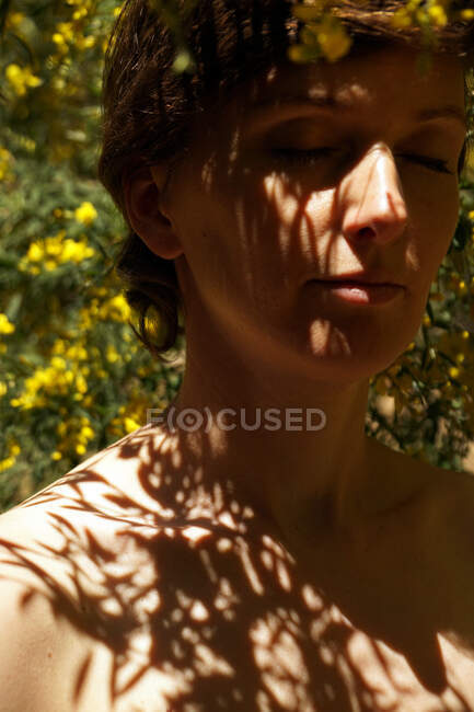 Calm adult naked female with closed eyes resting in garden near blooming tree with yellow flowers on sunny day — Stock Photo