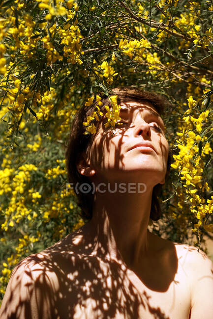 Low angle of calm adult naked female with closed eyes resting in garden near blooming tree with yellow flowers on sunny day — Stock Photo