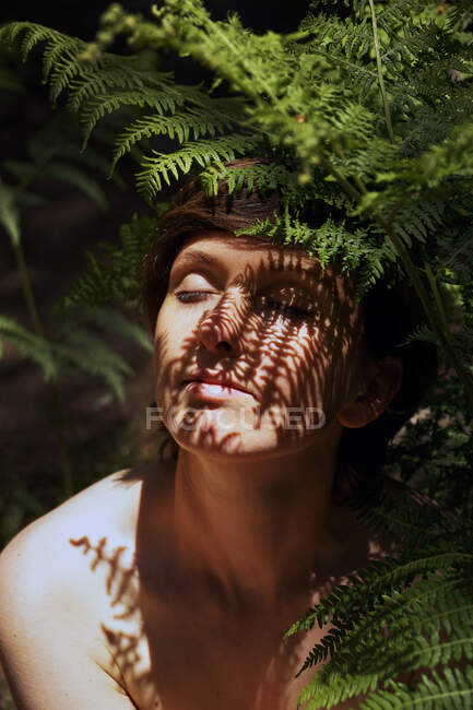 Alluring young naked woman with dark hair sitting near fern bush in lush tropical forest with eyes closed on sunny day — Stock Photo