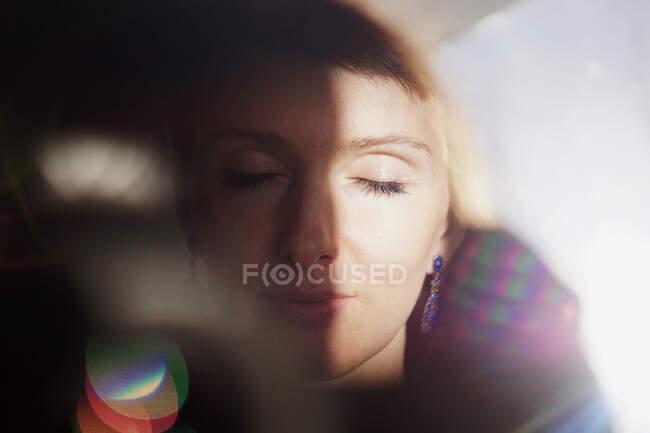 Через стекло мирной взрослой женщины с короткими волосами воссоздающей с закрытыми глазами в солнечный день — стоковое фото