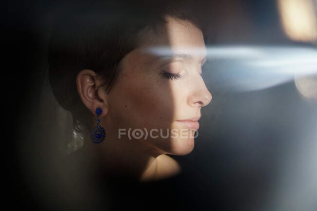 Through glass of peaceful adult lady with short hair recreating with closed eyes on sunny day — Stock Photo