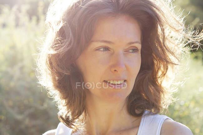 Ernte glückliche erwachsene Dame mit welligem Haar schaut verträumt weg, während sie sich in blühenden Wiesen an sonnigen Tagen auf dem Land erholt — Stockfoto