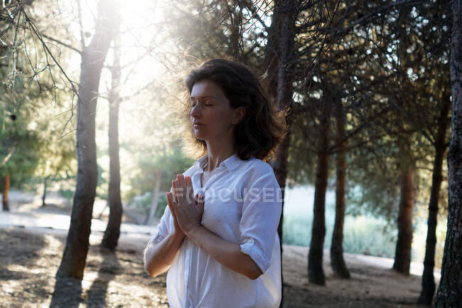 Side view of calm adult female in casual clothes meditating with closed eyes in forest on sunny day and practicing yoga — Stock Photo