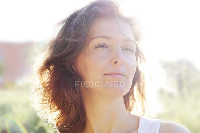 Crop happy adult lady with wavy hair looking away dreamily while recreating in blooming meadow on sunny day in countryside — Stock Photo