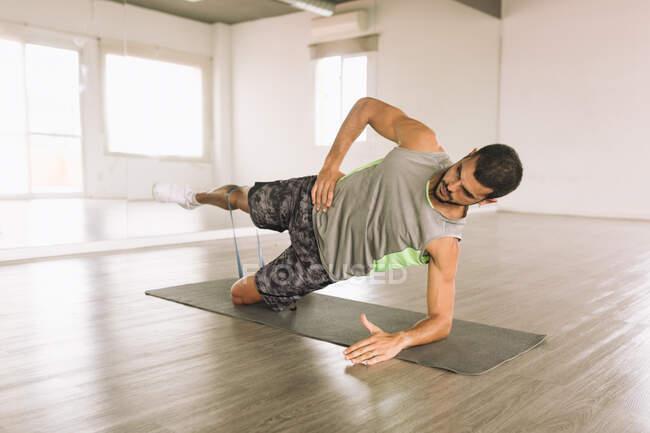 Повний набір молодих сфокусованих спортсменів в активаціях High Side Plank з вправами на ноги піднімає під час тренування в студії біля великого дзеркала стіни. — стокове фото