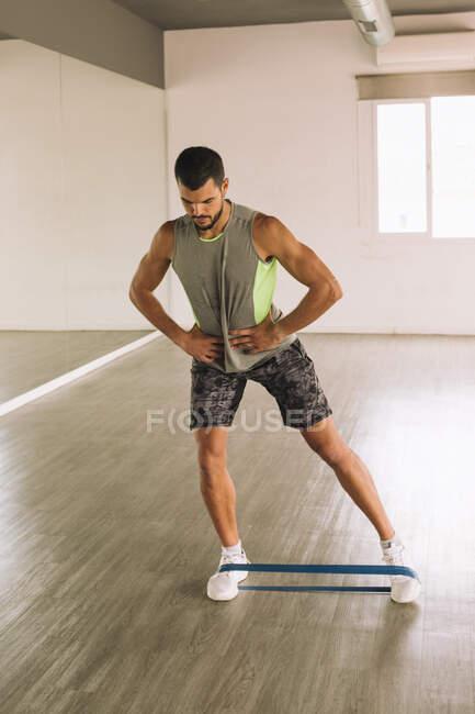 Сконцентрований молодий атлетичний хлопець у спортивному манері робить тренування Side Lunges з еластичною групою під час тренування на самоті в просторій фітнес-студії з дзеркалом — стокове фото