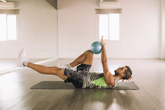 Side view of determined muscular young sportsman in activewear doing Leg Crunch exercise with medicine ball while lying on mat during workout in light studio — Stock Photo