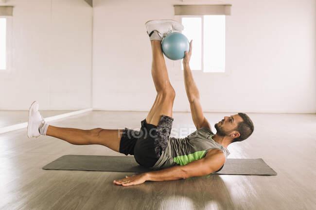 Vista lateral de determinado deportista joven muscular en ropa deportiva haciendo ejercicio Leg Crunch con balón de medicina mientras está acostado en la estera durante el entrenamiento en el estudio de luz - foto de stock