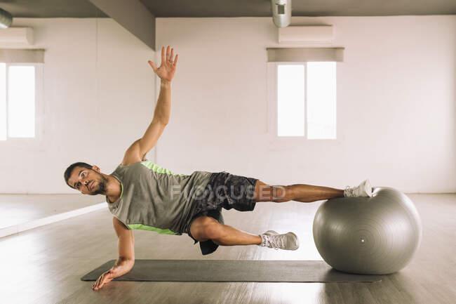 Longitud completa de un fuerte deportista muscular haciendo Side Star Plank en la pelota en forma durante el entrenamiento en el estudio - foto de stock