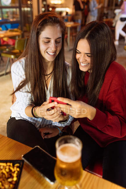 Young cheerful lesbian couple sitting at table with glasses of beer in cafe and using smartphone while spending weekend together — Stock Photo
