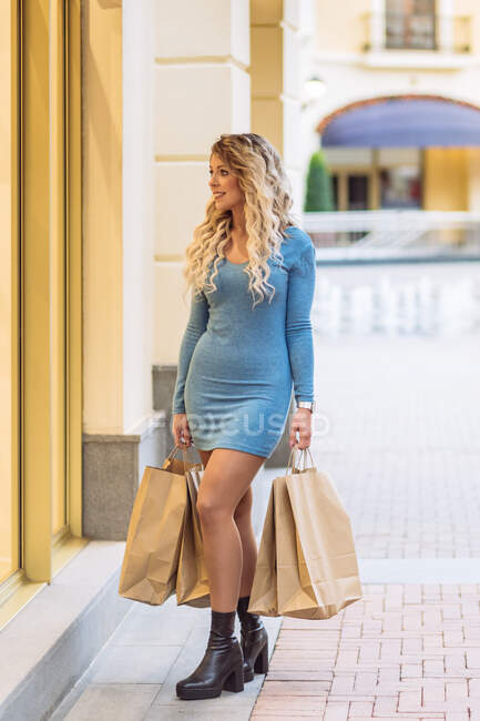 Content female standing with paper shopping bags near window of store in city street — Stock Photo