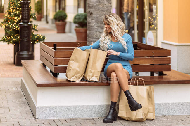 Glad female sitting on bench and looking at goods in shopping bags in city — Stock Photo