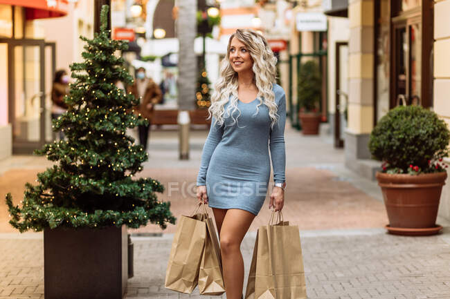 Happy female standing near christmas tree with paper bags in street with various shops and looking away — Stock Photo