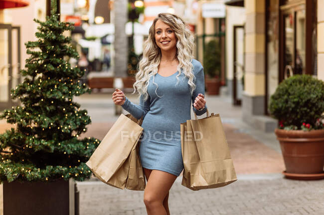 Happy female standing near christmas tree with paper bags in street with various shops and looking at camera — Stock Photo