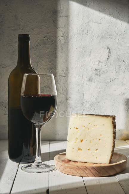 Arrangement of aromatic red wine in glass served on table near wine bottle and triangle cheese piece — Stock Photo